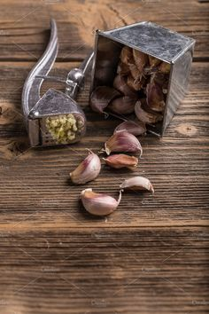 #Garlic press  Garlic press and garlic on wooden board