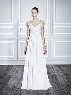 Moonlight Style T702Silver embroidered lace adorns the intricate illusion back and cap sleeves of this simple A-line wedding dress.