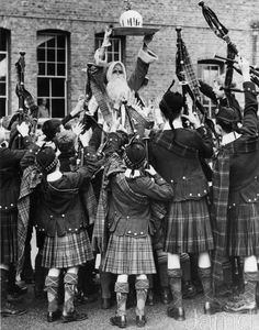 21st December 1935: Dr Barnardo boys of the Kingston Hill home chairing Santa Claus after piping him in. The boys are wearing highland dress and Santa holds aloft a large Christmas pudding. (Photo by Reg Speller/Fox Photos/Getty Images)