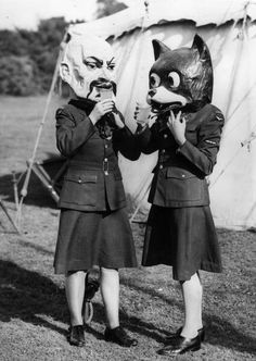 19th September 1945: Two Canadian airwomen wearing carnival heads have a drink at a victory party in Sudbury, Surrey. (Photo by Reg Speller/Fox Photos/Getty Images)