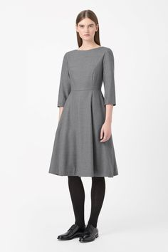 A tailored style, this fitted dress is made from lightweight wool with a slight stretch and subtle melange finish. Going in at the waist, it has a wide round neckline, 3/4 sleeves and a hidden zip fastening along the back.