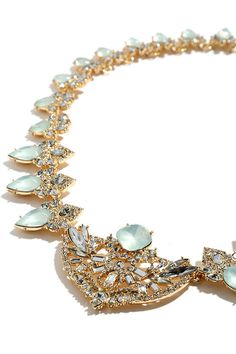 "A wonderland awaits the moment you put on the Ice Princess Gold and Mint Rhinestone Statement Necklace! An array of clear and mint rhinestones in gold settings create a dazzling display that will dress up any outfit. Includes a fun charm at back. Necklace measures 18"" around, with a 4"" extender chain."