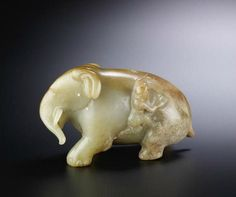 A rare pale green and brown jade carving of an elephant and man ...