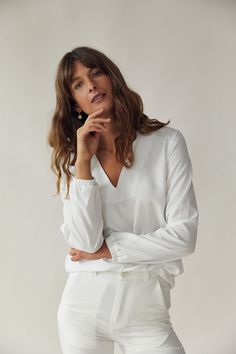 This is a white relaxed fitting blouse with long sleeves, a v-shaped neckline and an elastic band around the wrists. It is made of a very soft, luxurious fabric. We recommend tucking it in! 100% TENCEL™ fibers from Austria, woven in Spain and sustainably dyed using the Iris method. Made in Germany. V Neck Blouse, Ethical Fashion, Organic Cotton, Vogue, Label, Long Sleeve, Fabric, Austria, Iris