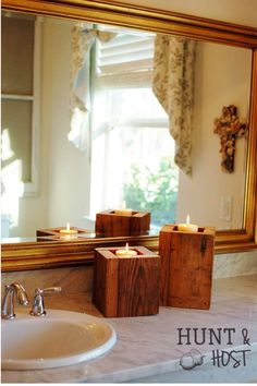 DIY salvaged wood candle boxes add a soft glow to this sparkling white bathroom. www.huntandhost.com