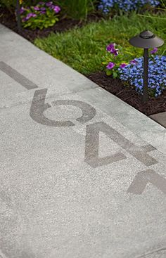 For a new approach to house numbers, apply Rustoleum's NeverWet to your sidewalk. When dry, the house numbers are subtle, but they really stand out when coated with rain. Like this treatment for the base of the driveway Outdoor Projects, Home Projects, Concrete Planters, Concrete Pad, Decks And Porches, Outdoor Living, Outdoor Decor, House Front, Curb Appeal