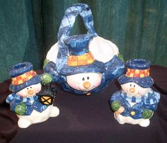 Snowman Holiday Basket Bowl and Candlesticks Centerpiece  Adorable Holiday centerpiece featuring a large bowl with matching candlesticks.  Snowman theme painted in bright colors of blue and creamy white and glazed in a high gloss finish. Bowl measures 8 inches X 10 inches X 7 inches. Each Candlestick snowman measures 5 inches X 4 inches. The bowls features a handle molded from the snowman's scarf.