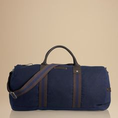 Make your move with this roomy duffle bag. Crafted from heavy waxed cotton with leather trims and striped webbing. Embossed Tommy Hilfiger logo between the leather carry handles. Accent webbed straps along the sides match the detachable and adjustable, webbed shoulder strap. Antique nickel hardware. Double-zip main compartment for ample room for all your gear. Blue plaid lining. This duffle is the perfect choice whether you're off to the gym or gone for the weekend.