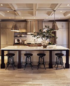 Distressed black bar stools and dark island pillars contrast against light travertine floors. Greenery and the range's red knobs offer hits of colour to a beige and grey palette, while gothic-style ar
