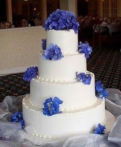 Four tier round white wedding cake with my favorite flowers fresh hydrangeas.