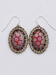 Bedazzling—these red glass cabochon earrings adorned with peacock swirls are encircled with a glittering rhinestone chain.