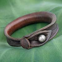 Sleek and somber, this leather bracelet accessorizes with casual elegance. The design is by Khun Boom of Thailand, who fastens the bracelet with a silver bell crafted by the Karen hill tribe people.