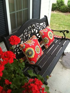 right side of my front porch with pillows I just whipped up for a pop of color to match geraniums and initial on front door may 2013