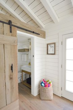 Whitewashed wood panels cover the walls and ceiling of this cottage. A rustic barn door slides open to reveal a white bathroom.