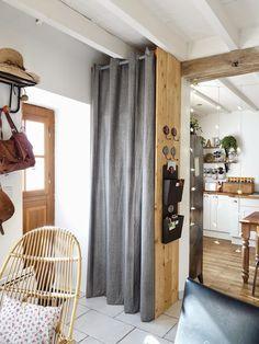 Une Penderie dans mon entrée. Placard entrée. coin salon, fauteuils salon, fauteuil bambou et rotin, guirlande lumineuse, armoire métallique, plantes vertes, table en bois, style industriel, style vintage, planches de coffrage. Vue de la penderie et de la cuisine depuis le coin salon.