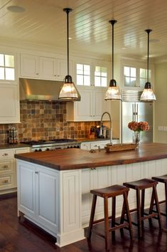 wood top on the island, pendant lights, small windows above the cabinets
