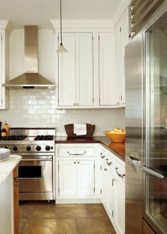 narrow stainless steel range hood with white subway tile back splash.