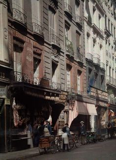 Vivid color photos of 1923 Paris, hub of artistry and progress. A street scene outside a butcher's shop.