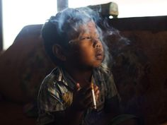 Dihan Muhamad, who used to smoke up to two packs of cigarettes a day before cutting down, poses for a photo as he smokes in his home. Picture: Michelle Siu