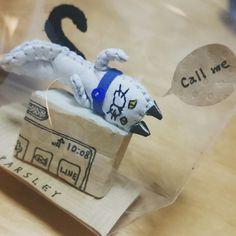 イヤホンジャック レザー 手縫い スマホの上に寝転がる猫