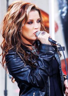 Lisa Marie Presley, singing in concert. Black leather jacket, streaked multi-colour hair. Rock on!