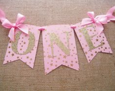 - First Birthday Banner - Light pink medium-weight cardstock - Gold foil star vellum overlay - Gold glitter letters 3 inches tall - Spans 12 inches from bow to bow - Additional 12 inches of satin ribb First Birthday Banners, Gold Birthday Party, Baby Girl First Birthday, Baby 1st Birthday, Birthday Numbers, First Birthday Parties, Birthday Ideas, Baby Shower Niño, Gold Baby Showers