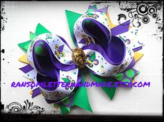 Big Beautiful Mardi Gras Hair Bow with a Glitter Gold Ribbon tie in the center. Bright Purple and Green Fleur de lis ribbons. The perfect