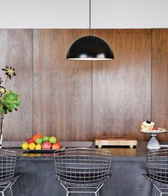 In the kitchen, custom walnut cabinetry and Caesarstone counters are paired with Bertoia stools and Ikea pendant lamps.   Photo by Ye Rin Mok.