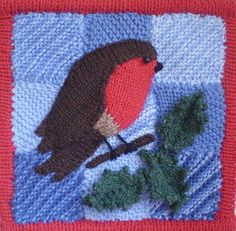 This is another of my small festive pictures, this time featuring a fat robin. The background is made up of garter stitch squares, knitted with odds and ends of blue yarn. The robin and his branch of holly are knitted separately and then sewn on to the quilt. The whole thing is surrounded by a knitted on binding which frames the picture and holds the wooden dowels which make the quilt hang straight.