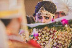 Well defined kohl eye makeup enhanced with dainty red bindi pearl and kundan studded maangtikka and pearled Mundavlya