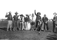 Rodeo cowboys and cowgirls raising coke bottles in arena, photo by R.R. Doubleday. From the Wyoming State Archives.