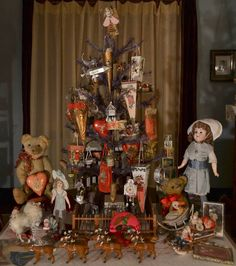 Antique Feather Tree decorated with antique Christmas tree candy containers. Antique Toys displayed under the tree.
