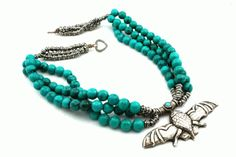 Tibetan necklace features three strands of beautiful teal blue turquoise beads connected in the center and back with multiple sterling silver spacers . It also features an amazing Tibetan Repousse Silver Bat with a Turquoise crown.
