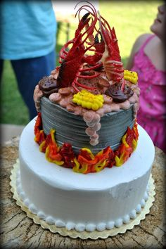 Our Cajun crawfish themed backyard wedding cake made of all frosting with crawfish pot boiling corn & potatoes. The topper is 2 rubber crawfish!