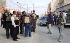 Armed tribesmen and Iraqi soldiers stand guard in a street as clashes rage on in the Iraqi city of Ramadi, January 2014.