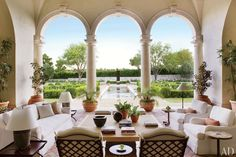 The loggia, whose custom-made sofa and club chairs are covered in a Perennials outdoor fabric, overlooks boxwood parterres designed by Robert E. Truskowski and a reflecting pool that culminates with John McCracken's sculpture White Light.