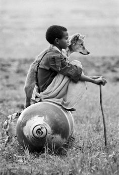 A Young boy sitting on an unexploded bomb dropped by Mengistu forces in Tigray, north Ethiopia. 1991. Photo by © Dario Mitidieri.
