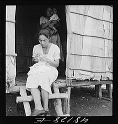Title: Utuado, Puerto Rico (vicinity). Stitching needlework at the home of a farm labor family in the hills. It is a widespread practice for factories to distribute hand work in this way
