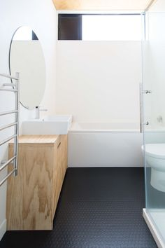 Clean and simple bathroom with a black rubber floor, a white tub and a round mirror. #rubberflooringideas