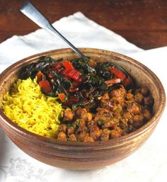 A healthful bowl of curried chickpeas with onions, tomatoes, and spices, served with some fragrant turmeric rice and garlicky sauteed Swiss chard.