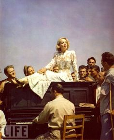 """""""At an evacuation hospital near the Italian front lines, Marlene Dietrich sits on a piano while wounded troops gather around to listen to her sing, May 1944."""""""