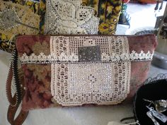 rug clutch, made from a vintage rug, leather belt handle, vintage crochet, and buckle