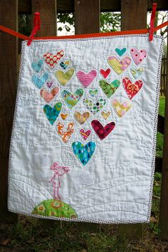 quilt with hearts made from old baby clothes.