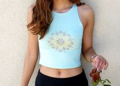 A mandala sunshine medallion embroidered on an American Apparel sleeveless spandex crop top is both form fitting and comfortable. This shirt falls