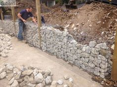 gabion wall construction, fence posts set between gabions. http://www.gabion1.com