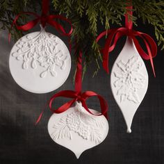 Shop Stamped Porcelain Ornaments. Displaying silhouettes of traditional ornament shapes, our matte white porcelain ornaments are stamped with a sculptural holly, pine bough or mistletoe sprig, accented with red grosgrain ribbon hangers.