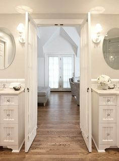 Elegant ensuite bathroom with warm oak floors and double vanities