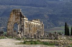 the afternoon sun shines on the arches of the Basilica, the main administrative building in the ancient Roman city of Volubilis, near Meknes, Morocco