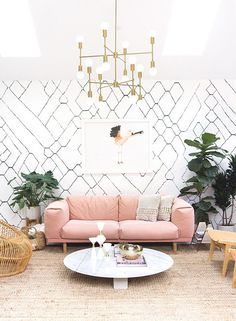 Contemporary eclectic living room home decor ideas with pink sofa, marble coffee table, Bohemian rattan chairs, wallpaper, and glamorous lighting