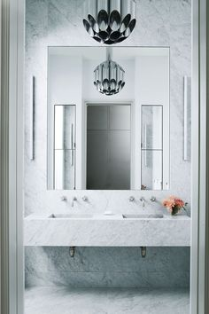 A sleek white marble SoHo loft bathroom is clad in marble, from floor to ceiling.